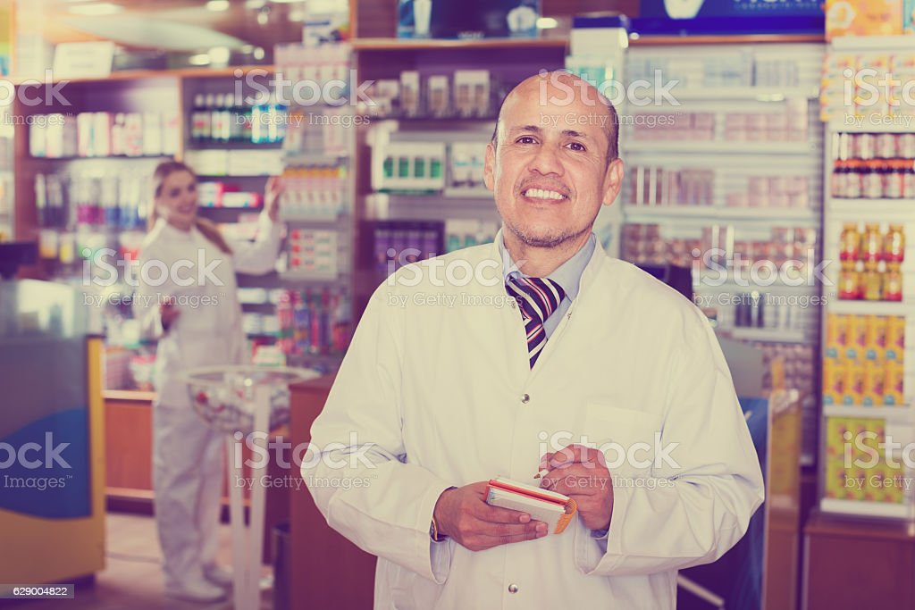 Two pharmacists in chemist shop stock photo