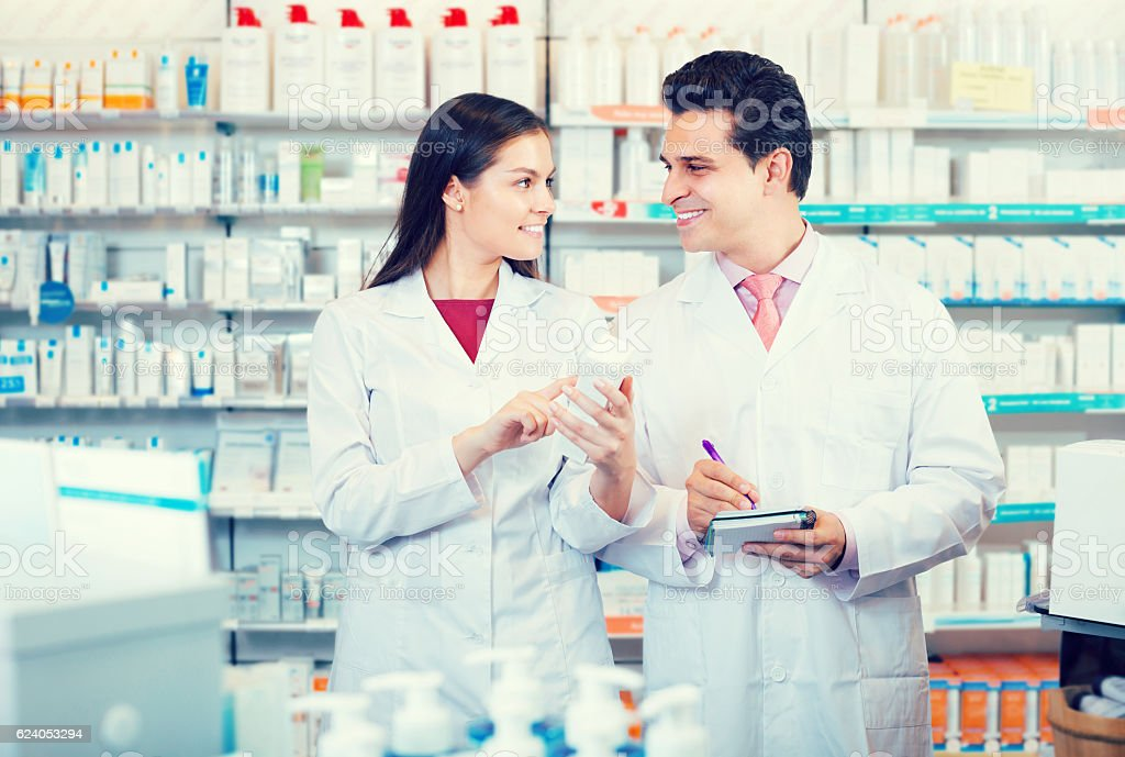 Two pharmacists in modern pharmacy stock photo