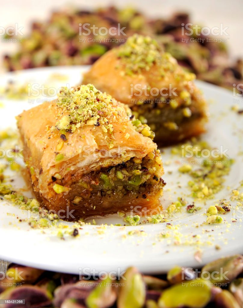 Two pieces of Baklava covered in pistachio on a white plate stock photo