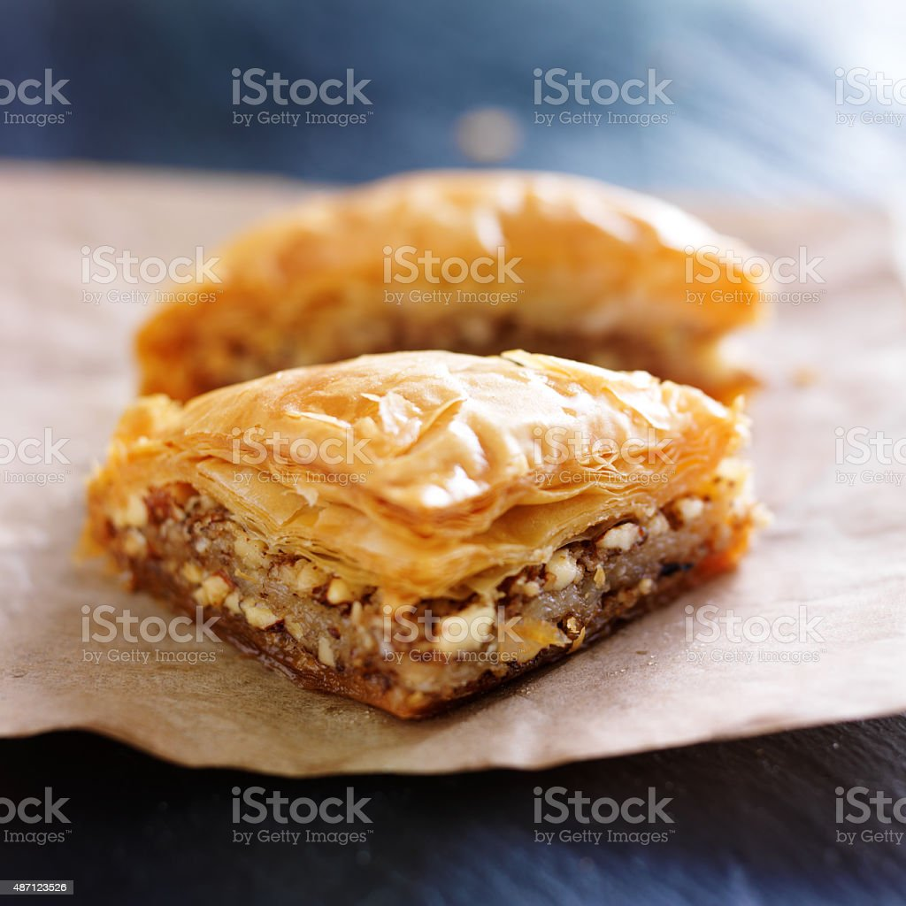 two pieces of baklava on wax paper stock photo