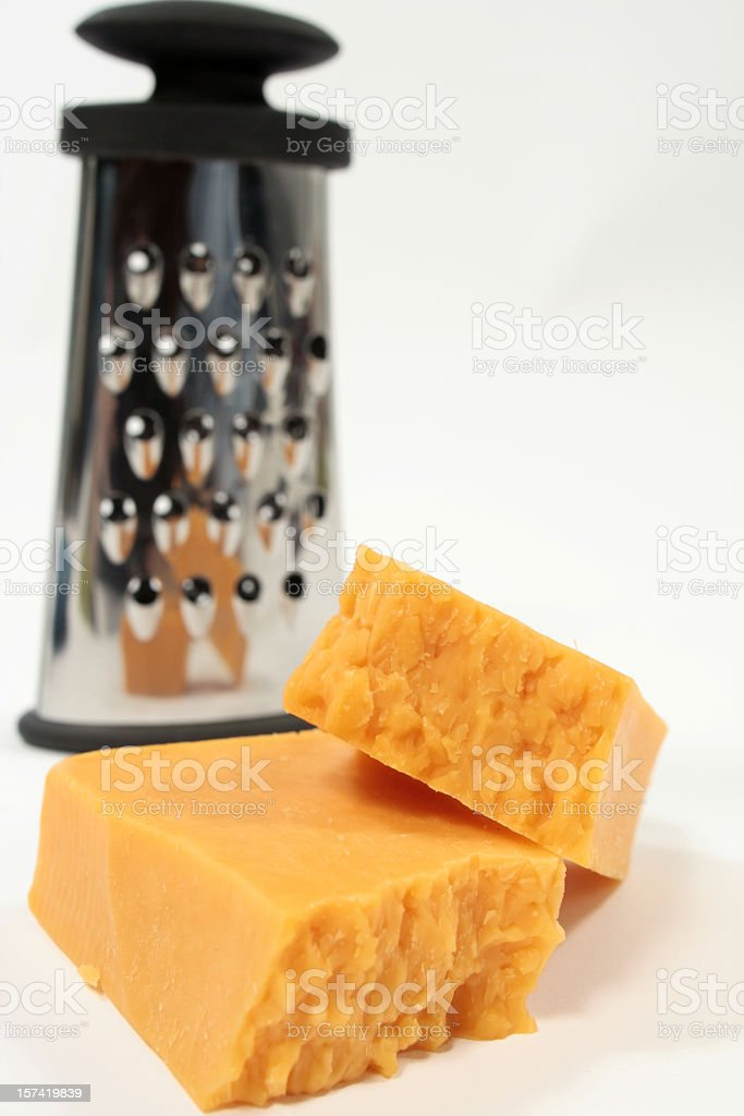 Two pieces of cheese with shredder out of focus in the back stock photo