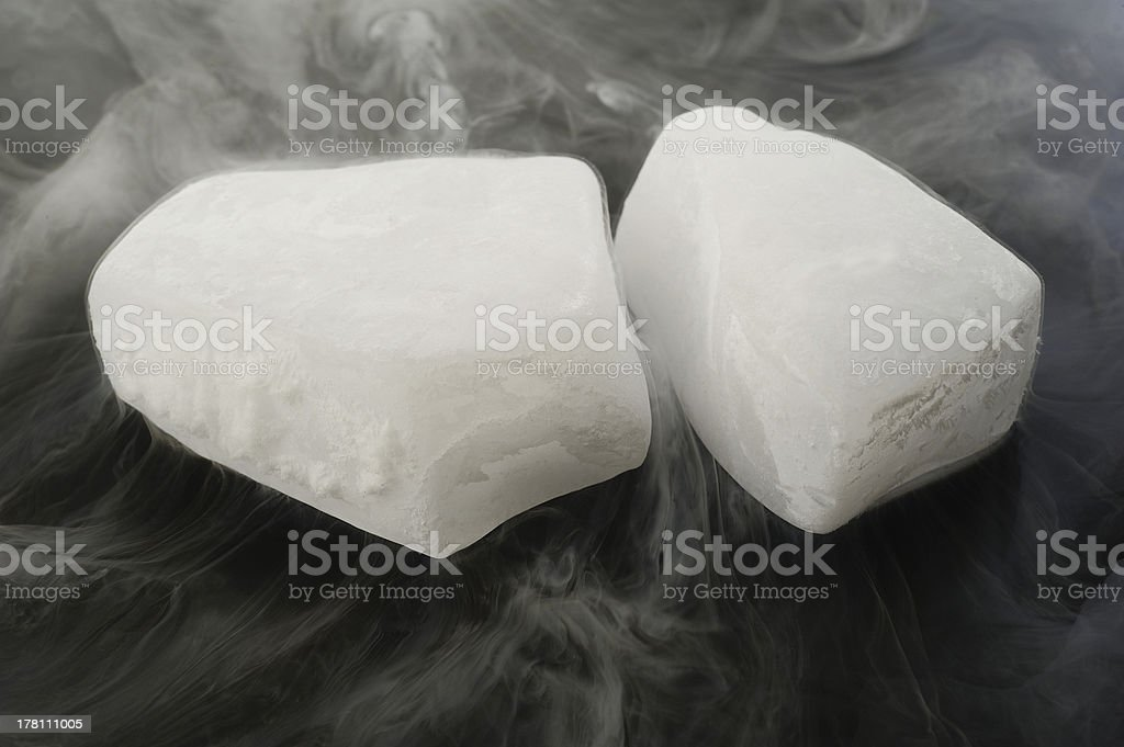 Two pieces of dry ice smoking against a dark background stock photo