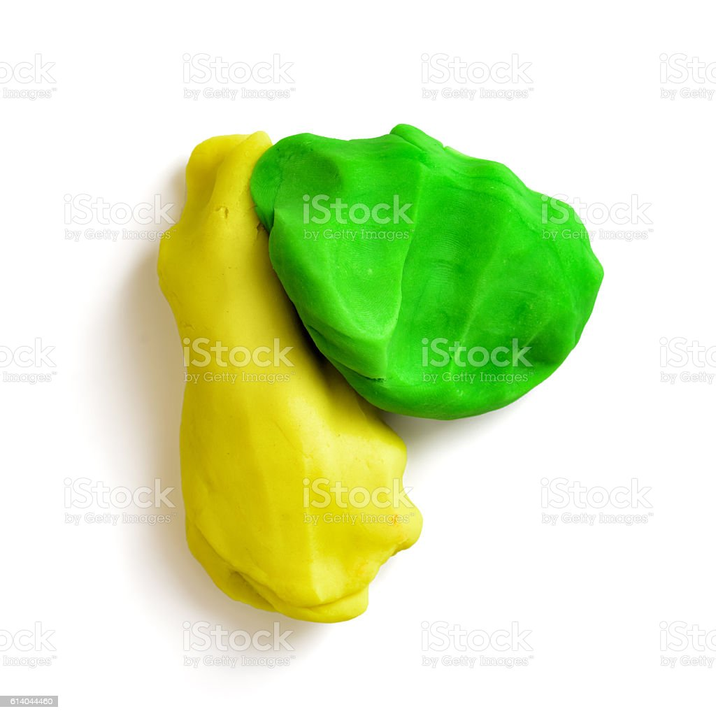 Two pieces of plasticine, yellow and green, isolated on a stock photo