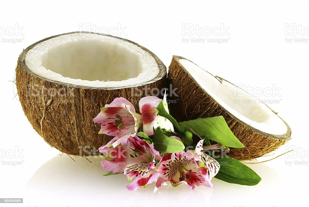 two pieces of ripe coconut with flowers royalty-free stock photo