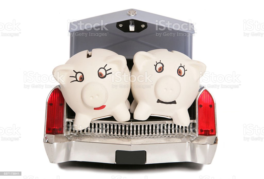 two piggy banks in car boot stock photo