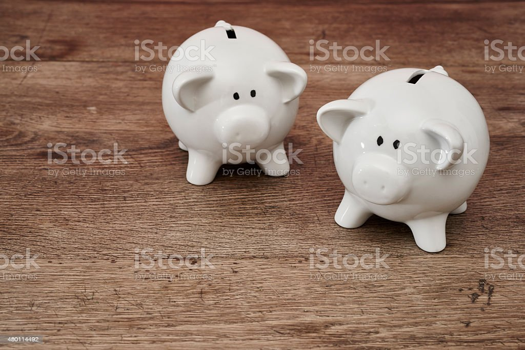 Two piggy banks on table stock photo