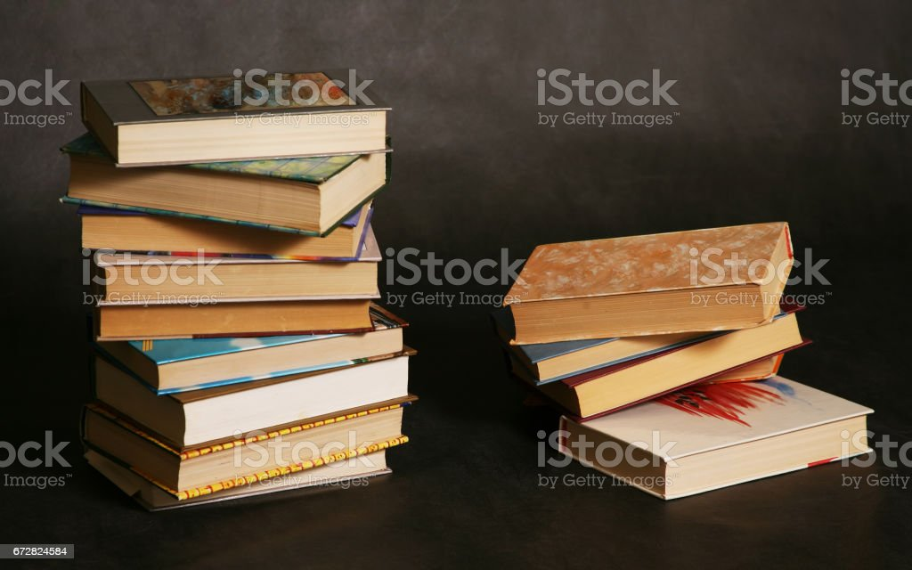 Two piles of books in different bindings in studio stock photo