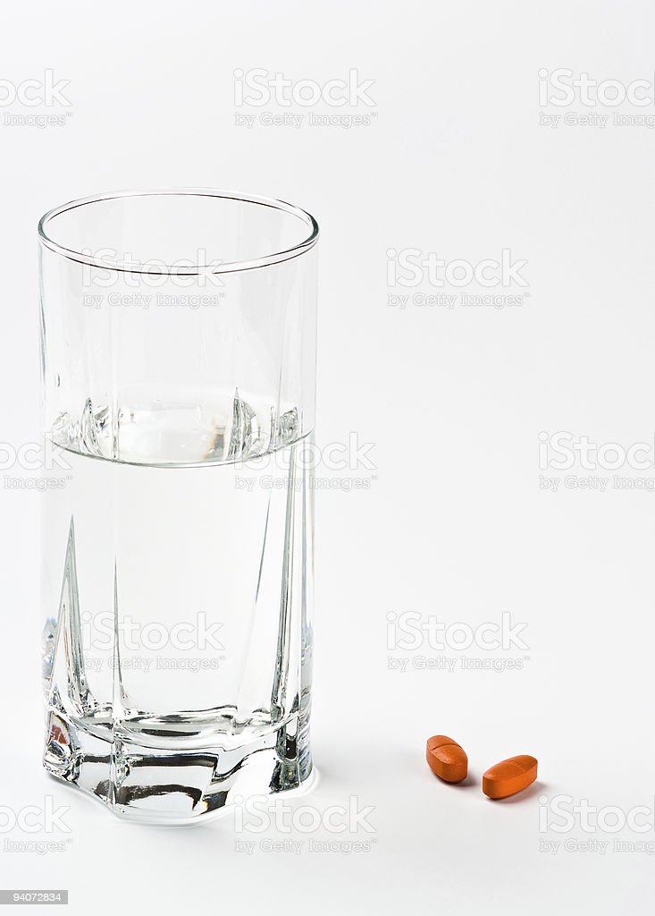 two pills and glass of water royalty-free stock photo