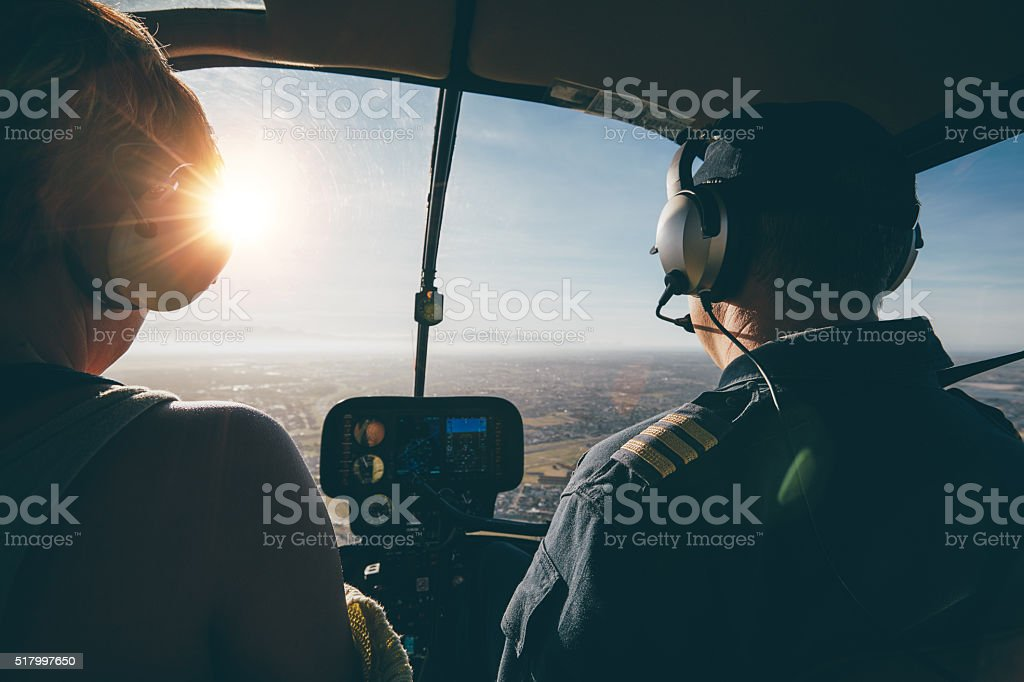 Two pilots in a helicopter flying on a sunny day stock photo