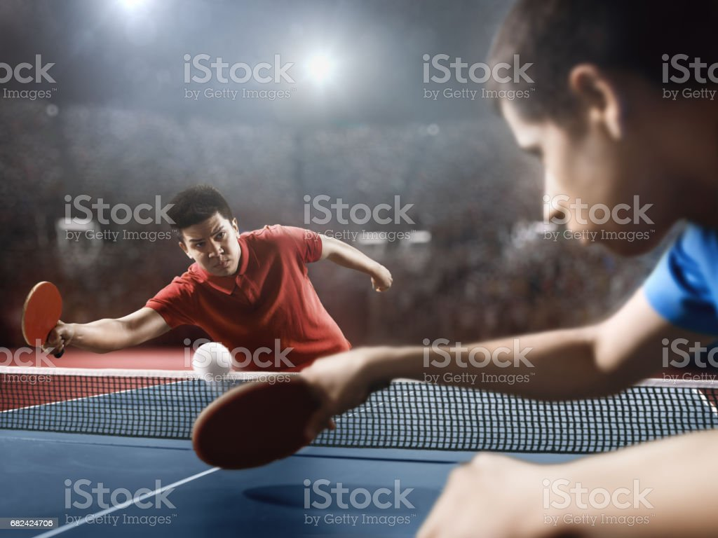 Two ping pong players play table tennis. One is dressed in a red...