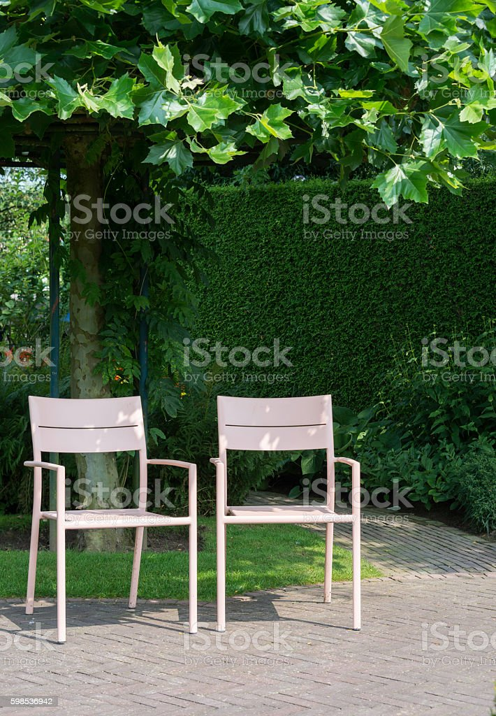 two pink seats in garden stock photo