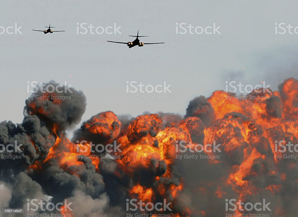 Two planes flying over a big exploding fire with dark smoke stock photo