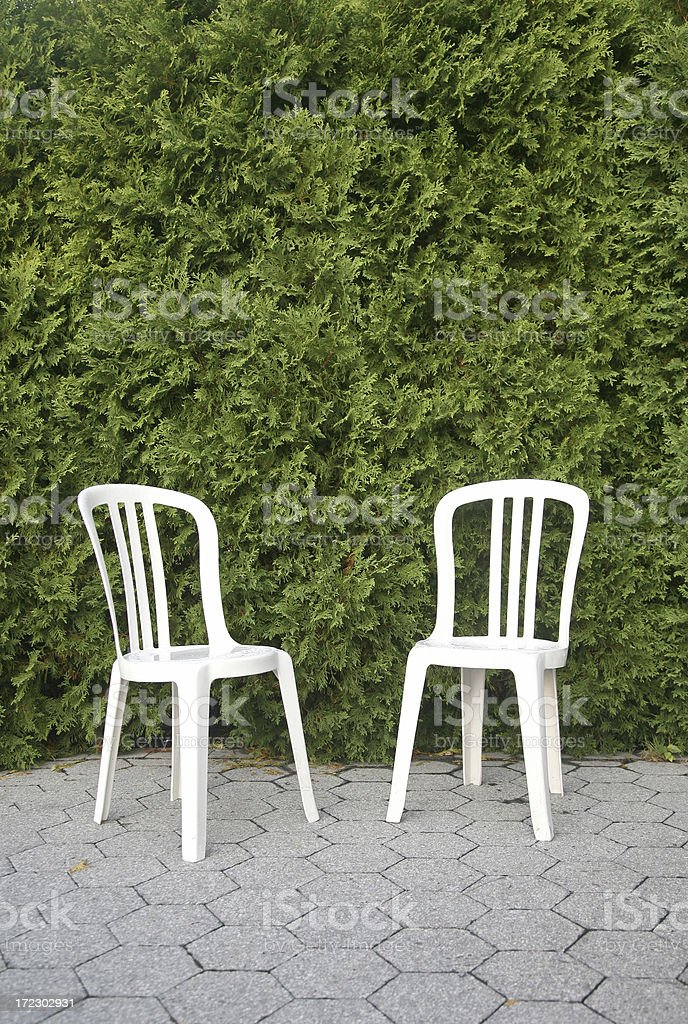 Two Plastic Chairs In Front Of Hedges royalty-free stock photo
