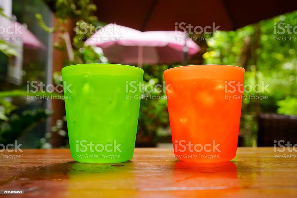 two plastic glass with straw on wooden background stock photo