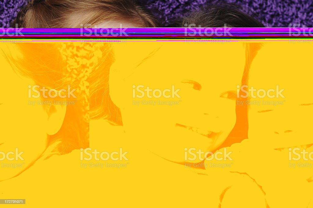 Two Playful Sisters Lying on Purple Carpet royalty-free stock photo