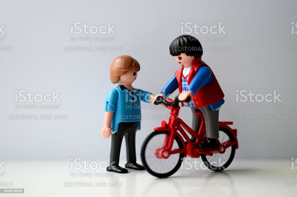 Two playmobil ,one on a bike. stock photo