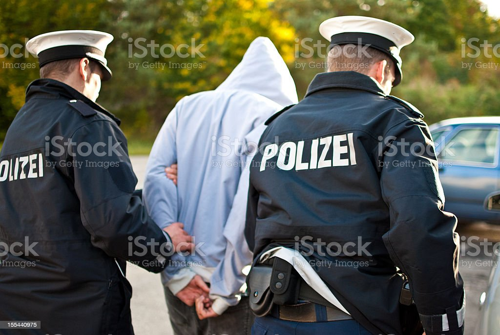 Two police officers are frogmarching a suspect stock photo