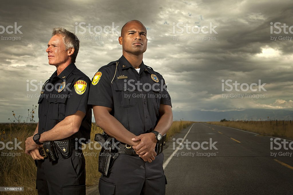 Two police officers standing on quiet road stock photo