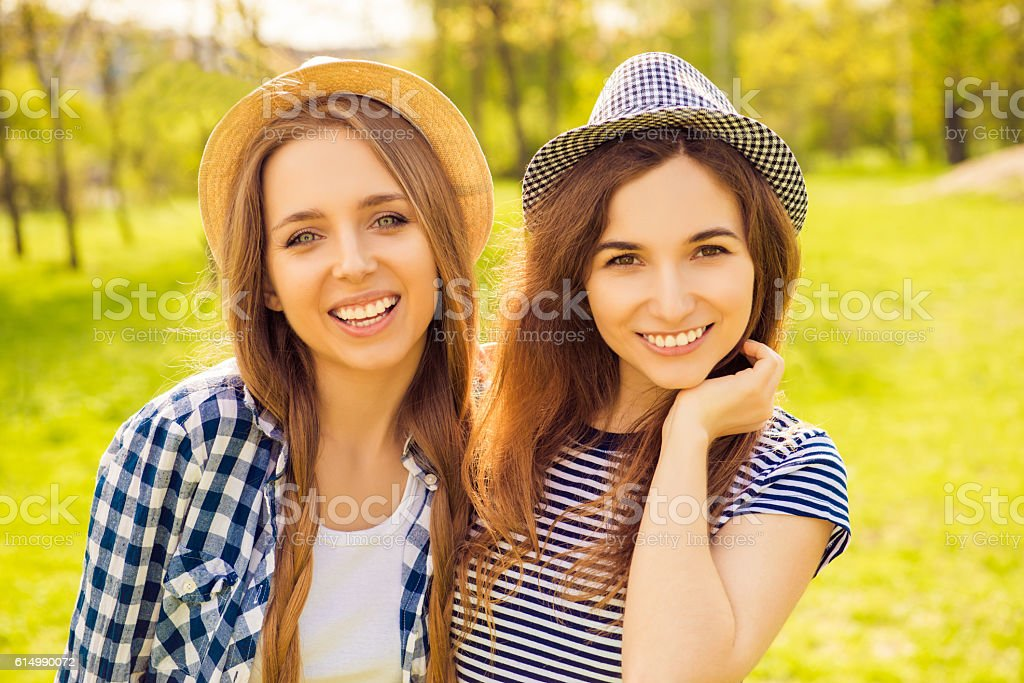 two positive smiling girls in caps walking in the park stock photo