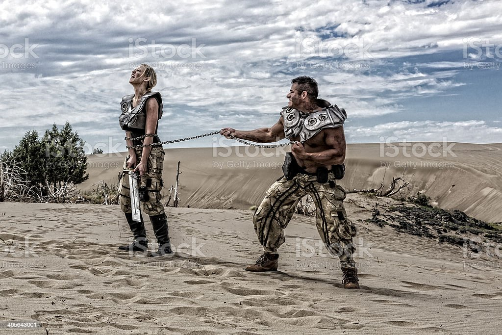 Two post-apocalyptic warriors do battle in the parched desert stock photo