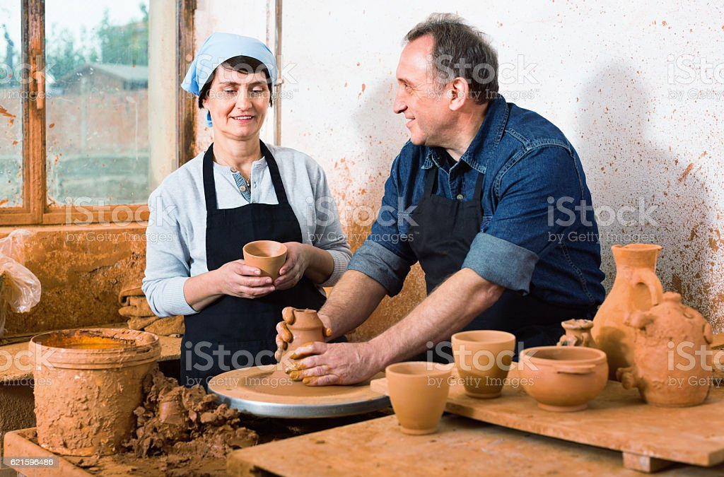 Two potters in the process of work at the workshop stock photo