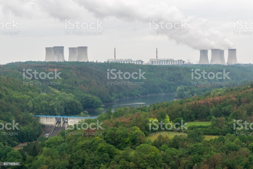 Two power plants, hydro powerplant in the valley and nuclear power plant on the horizon stock photo