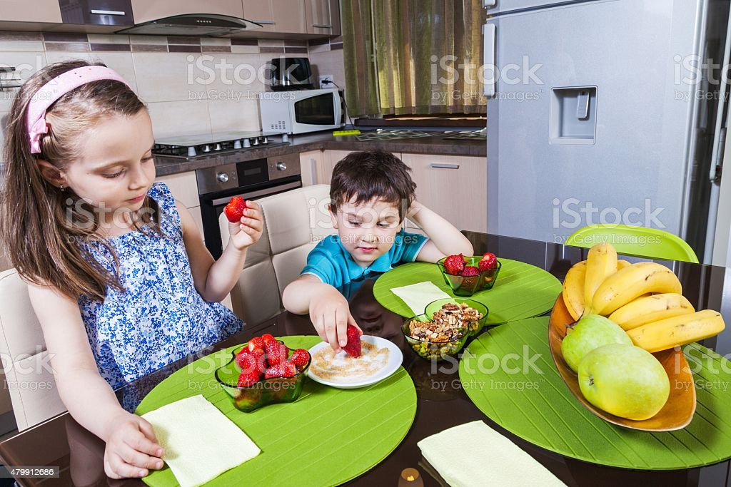 Two preschool children eat strawberry in the kitchen stock photo