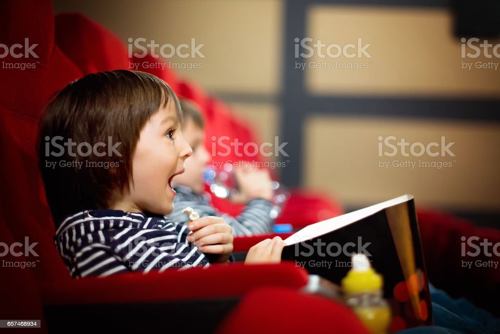 Two preschool children, twin brothers, watching movie in the cinema, eating popcorn stock photo