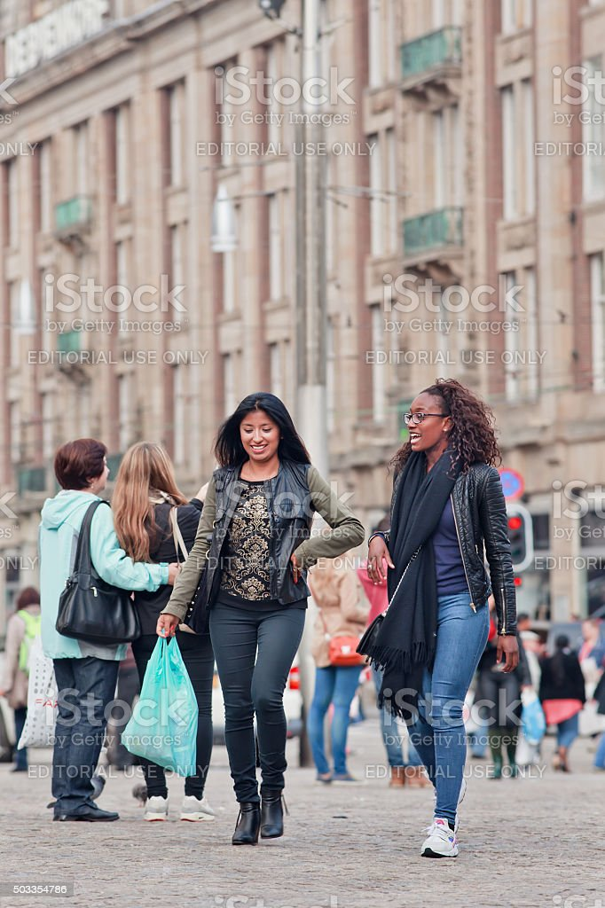 Two pretty exotic girls walk at Amsterdam Dam Square stock photo