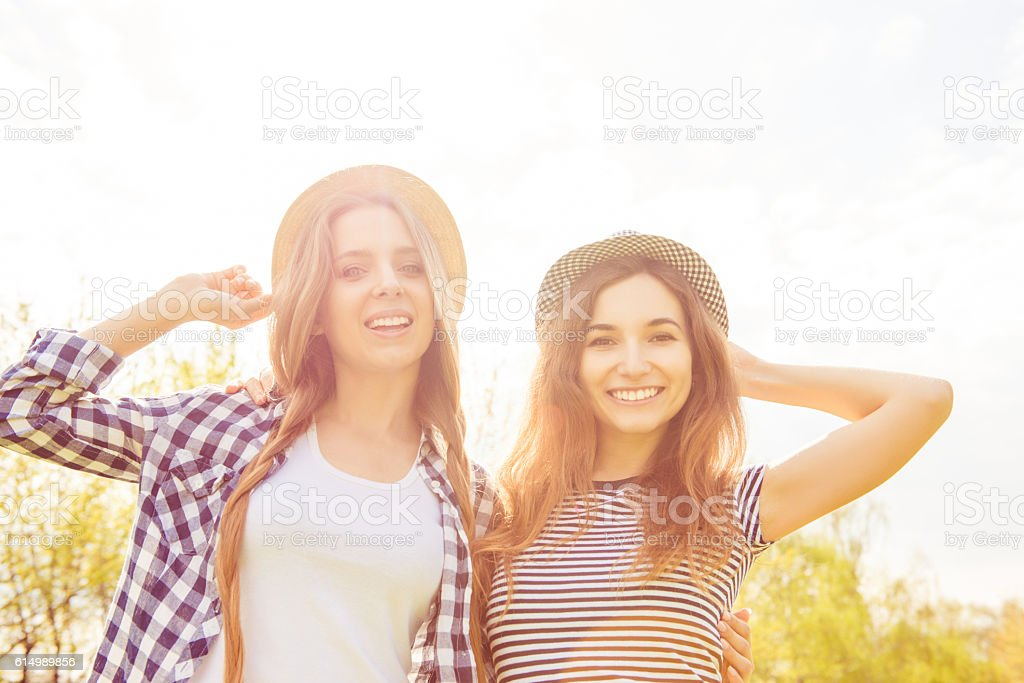 two pretty girls in hats walking in the park stock photo