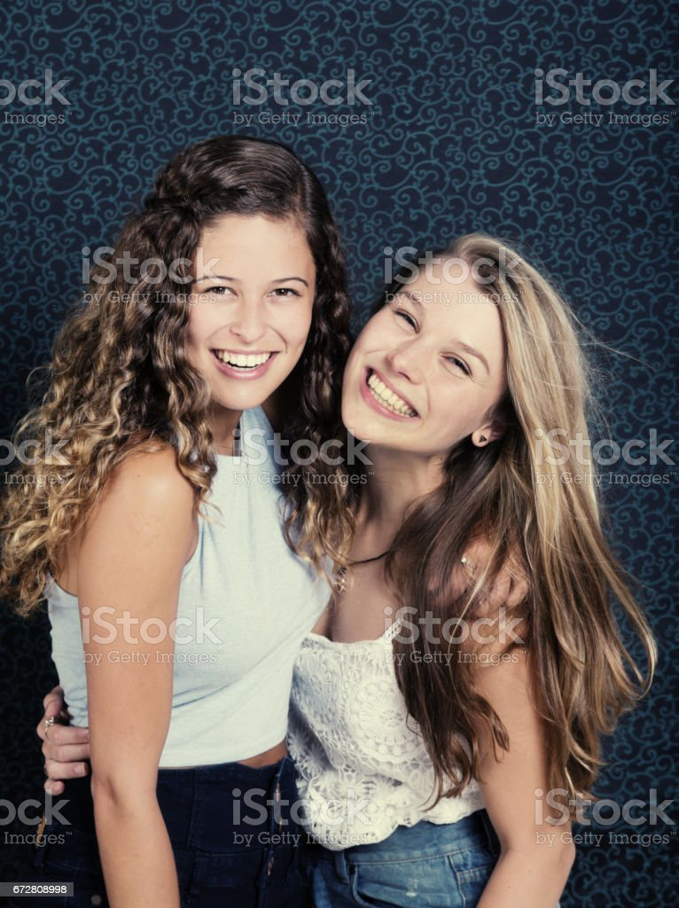 Two pretty girls smile happily, arms around each other stock photo