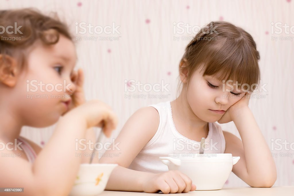 Two pretty little girls eating without appetite stock photo