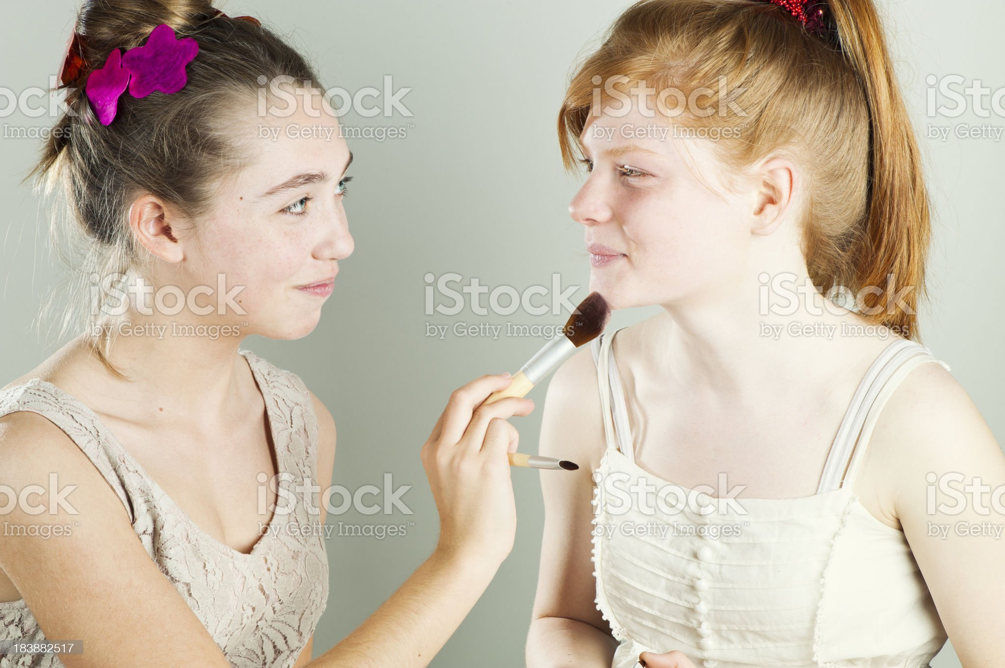 Two pretty teenagers putting make-up. royalty-free stock photo