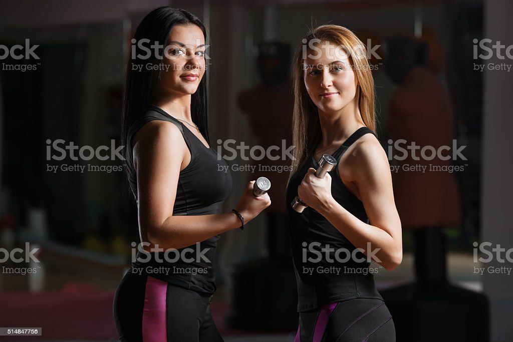 Two pretty weman with dumbbells stock photo