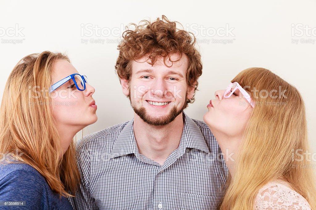Two pretty women kissing handsome man. stock photo