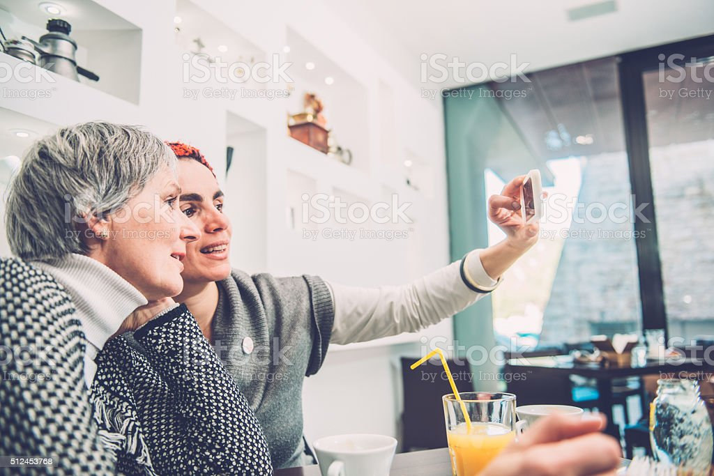 Two Pretty Women Taking Selfie  Caffe Trieste, Europe stock photo