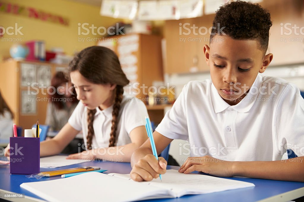 Two primary school pupils at their desks in class, stock photo