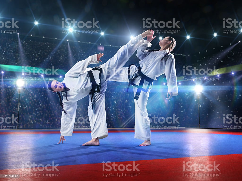 Two professional female karate fighters are fighting stock photo