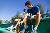 Two professional players hydrating after a hard game of tennis.