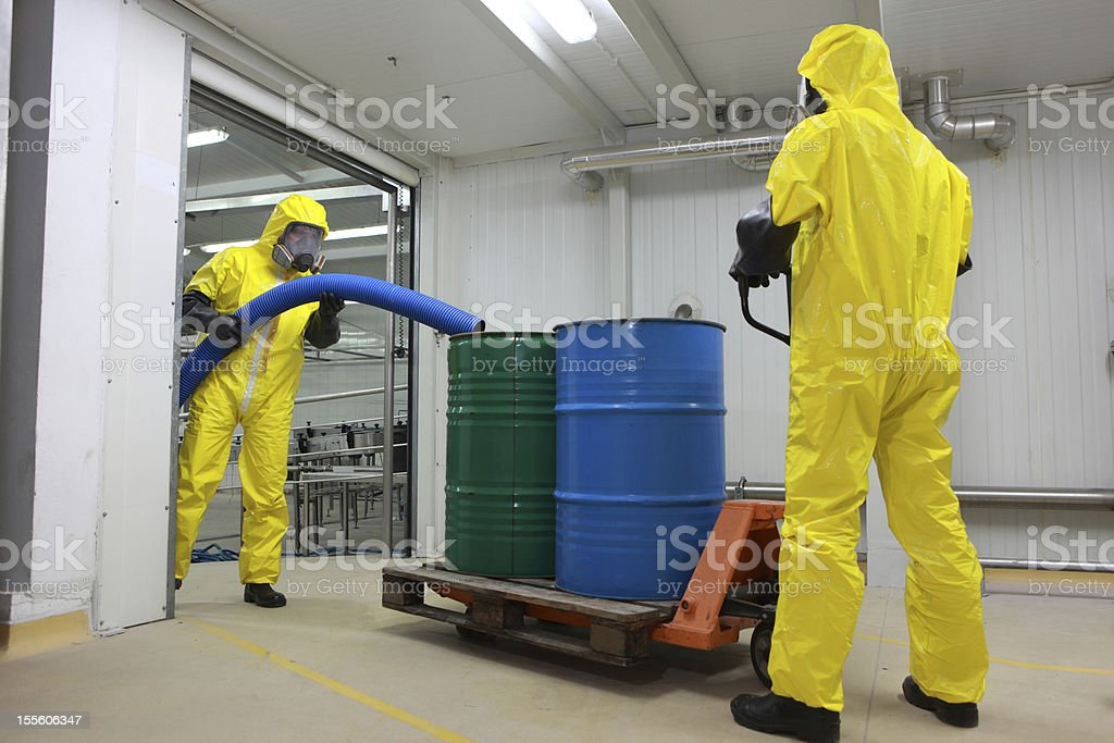 two professionals in uniforms dealing with chemicalss stock photo
