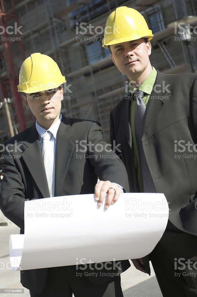 Two project leader looking the plan at building site royalty-free stock photo