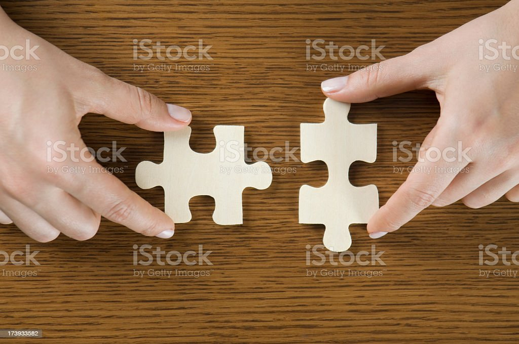Two puzzle pieces about to fit together on a wooden surface royalty-free stock photo