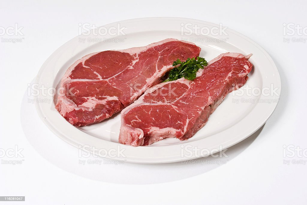 Two Raw New York Strip Steaks isolated on white stock photo