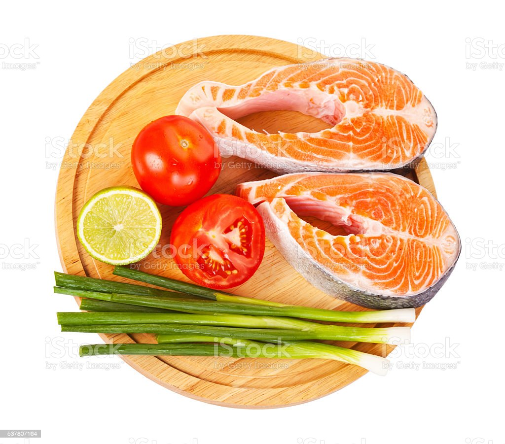 Two raw salmon steaks with tomatoes stock photo
