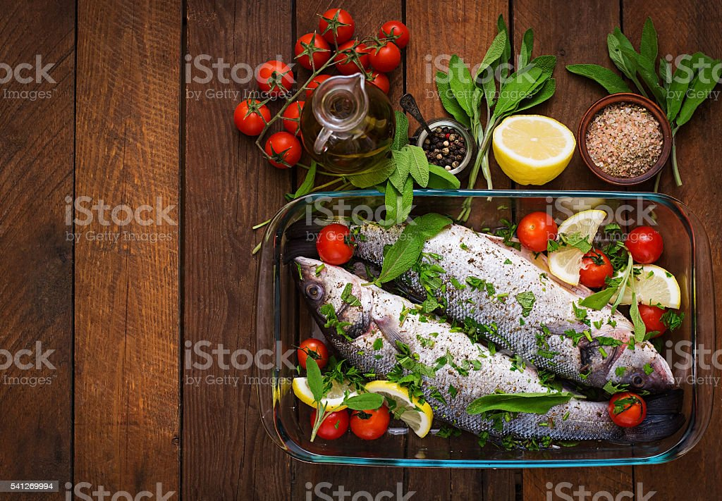 Two raw seabass in a baking dish with spices stock photo