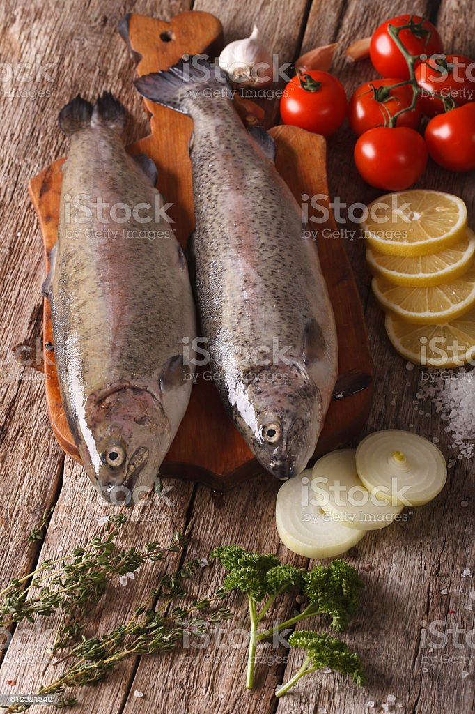 Two raw trout with ingredients on a cutting board. vertical stock photo