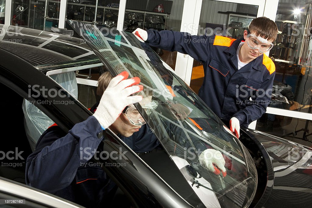 Two Real Mechanics working  in Auto Repair Shop. stock photo