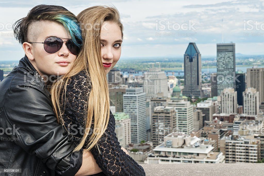 Two rebel teenagers hugging in front of Montreal cityscape. stock photo