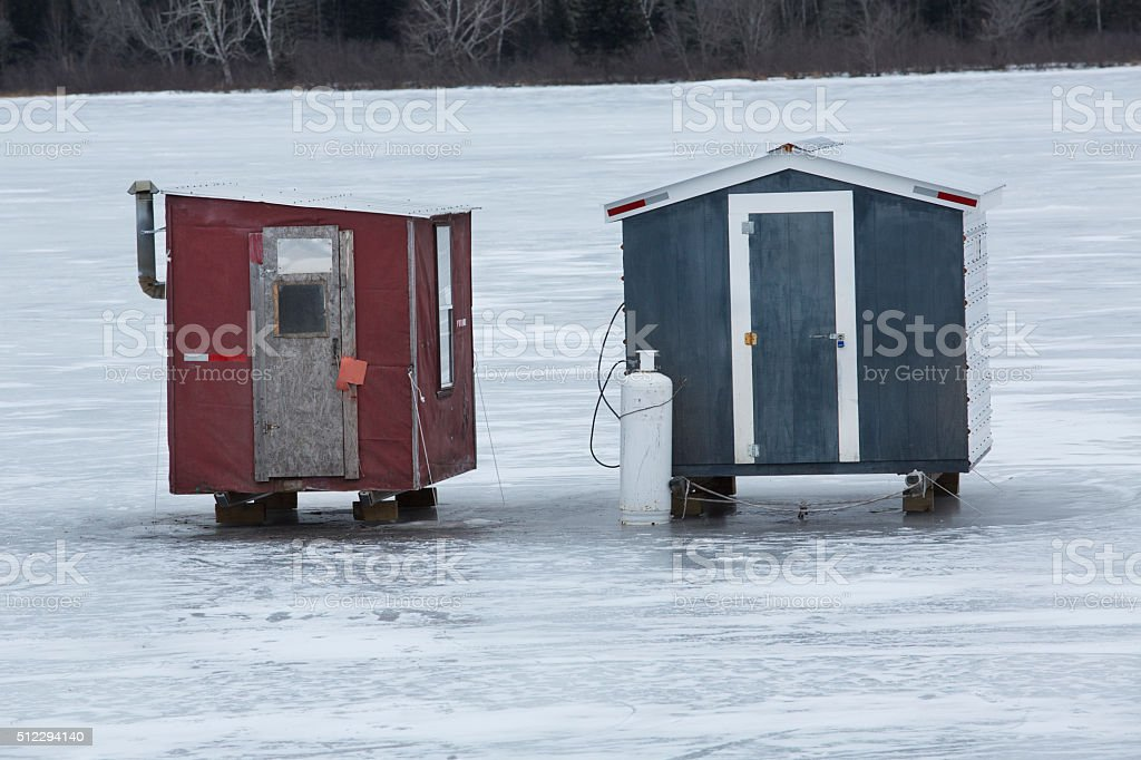 Two red and gray ice fishing shelters, Errol, New Hampshire. stock photo