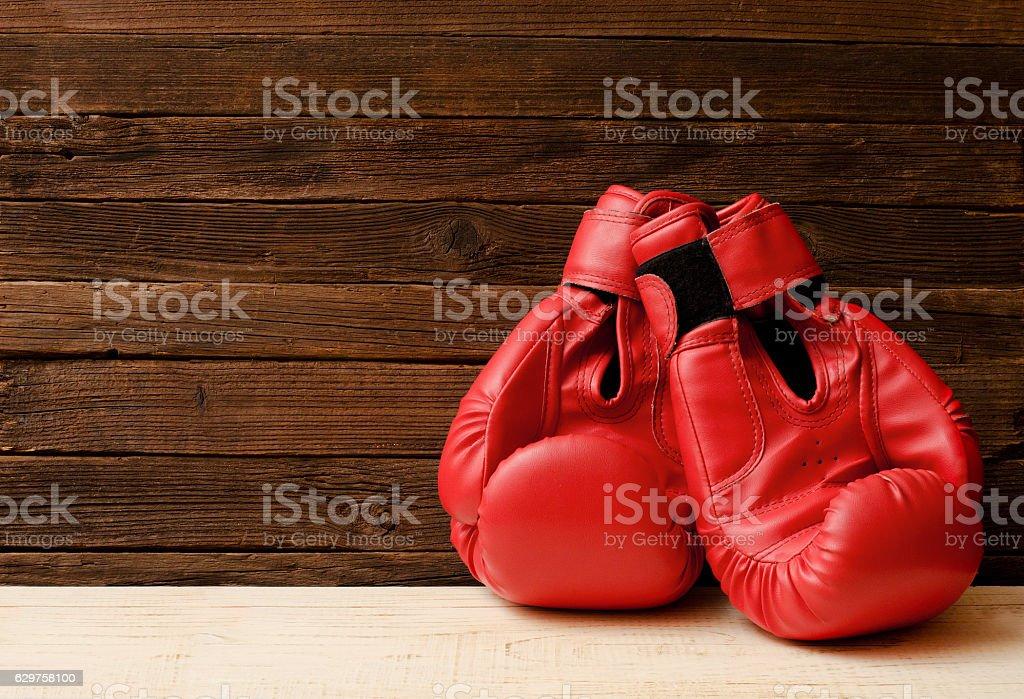 Two red boxing gloves on a wooden brown background stock photo